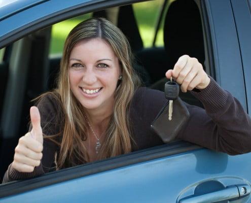 Fahrschülerin in ihrem Auto nach bestandener Fahrprüfung