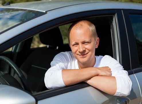 Foto eines Fahrlehrers, der lächelnd aus dem Fenster seines Fahrschulautos schaut