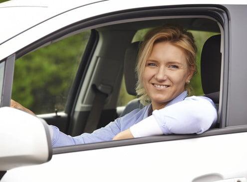 Foto einer jungen Fahrlehrerin, die aus dem Fenster ihres Fahrschulautos sieht