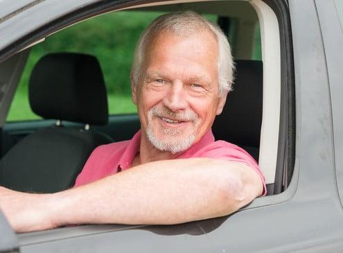 Foto eines älteren Fahrlehrers, der aus dem Fenster seines Fahrschulautos sieht