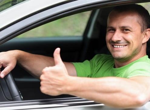 Foto eines jungen Fahrlehrers, am Steuer seines Fahrschulautos